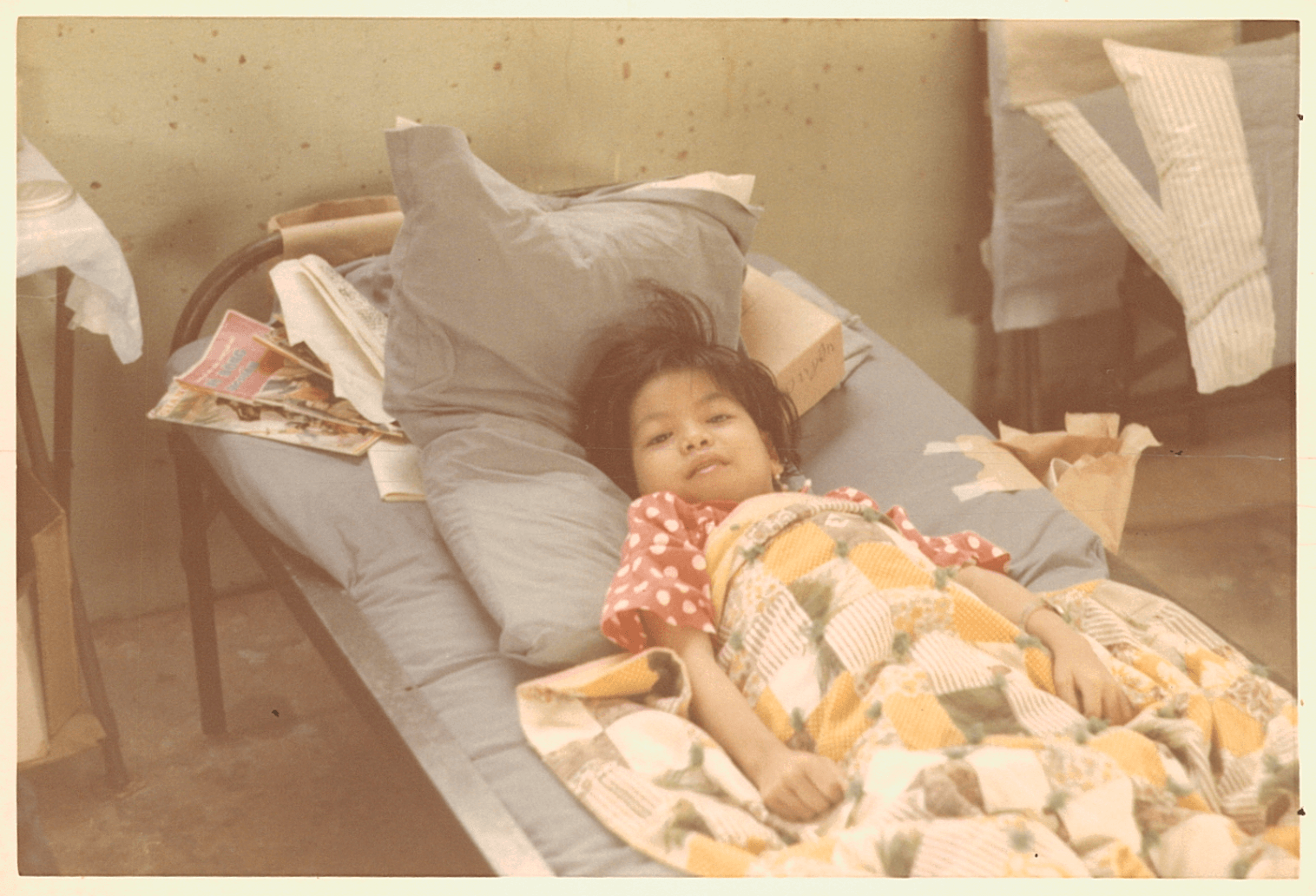 A young Asian child in her hospital bed, under a colorful quilt.