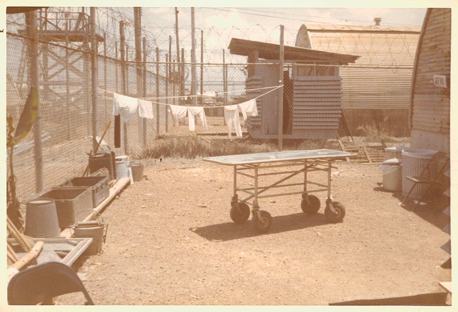 The yard of the hospital, dirt floor, clothesline, metal hospital bed.