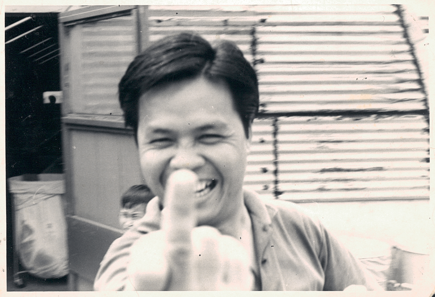 A young Asian man flipping off the camera, big grin on his face.