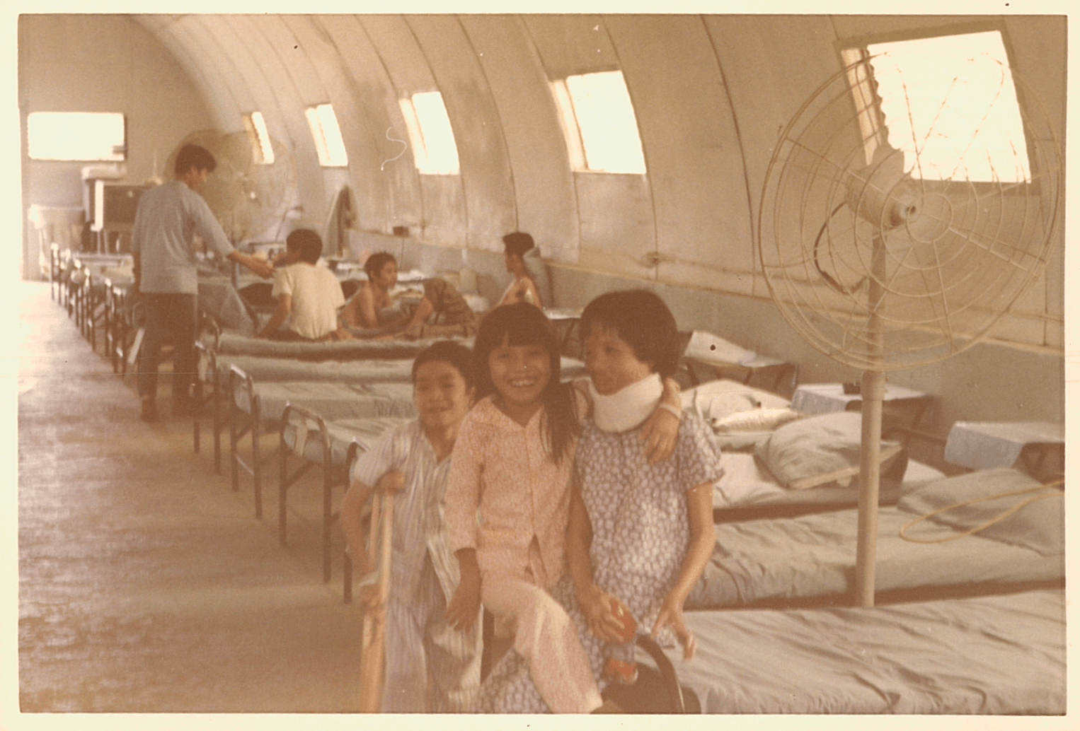 Two young Asian girls smiling from their bunks in the ward.