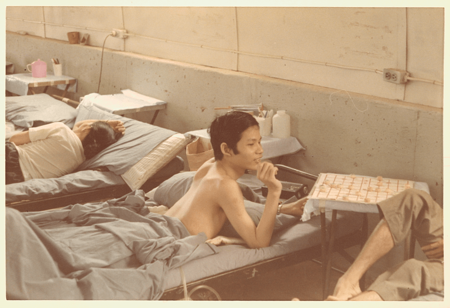 An Asian boy recuperates from his hospital bed, laying on his stomach.