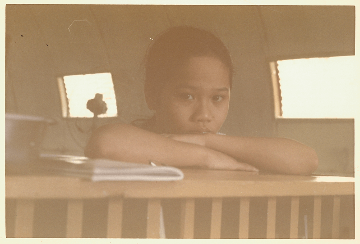 A young Asian girl peers somberly over her bed toward the camera.
