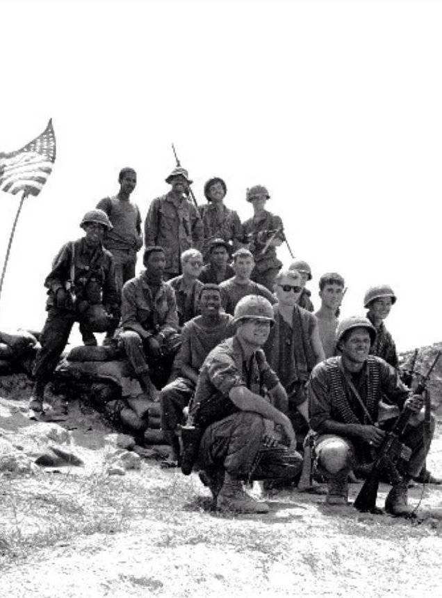 A group of U.S. soldiers pose on a hill, the American flag waving off to the left.