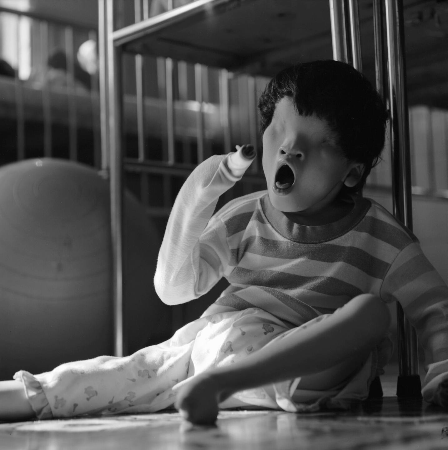 An Asian child without eyes, mouth agape, seated on the floor next to a crib.