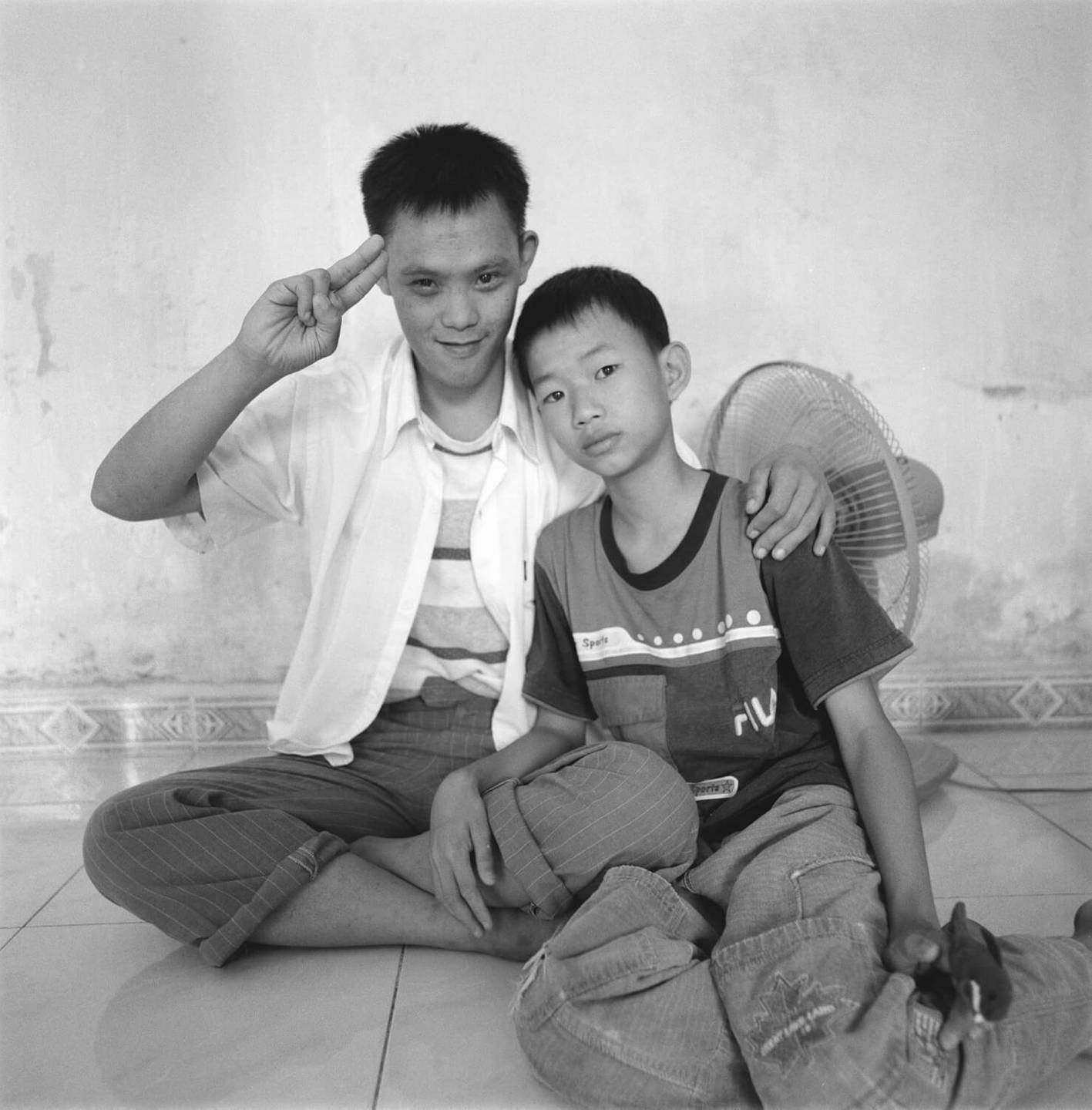 Two young Asian men seated on a tile floor. The older appears deformed and is doing a two-finger salute.