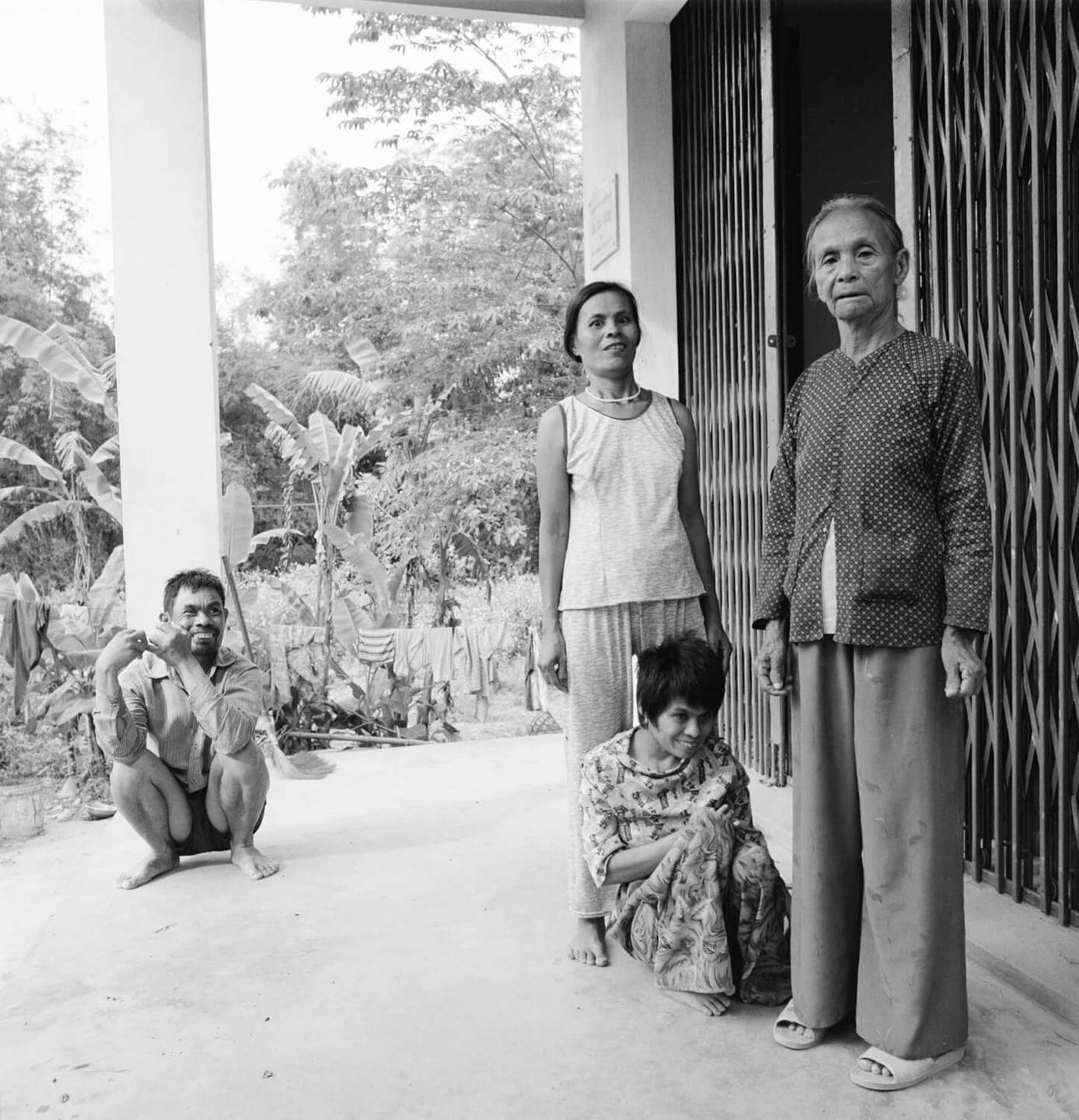 An Asian family of four outside their abode. The three youngest appearing to be deformed.
