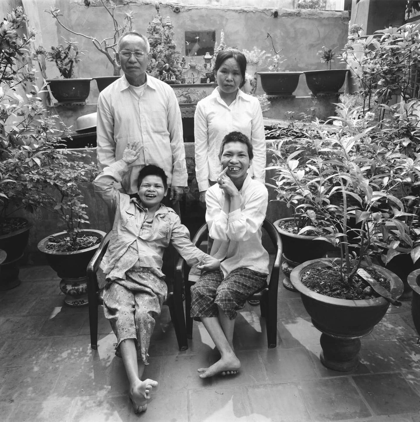 An older Asian gentleman with his three daughters, two of whom are deformed, in a courtyard.