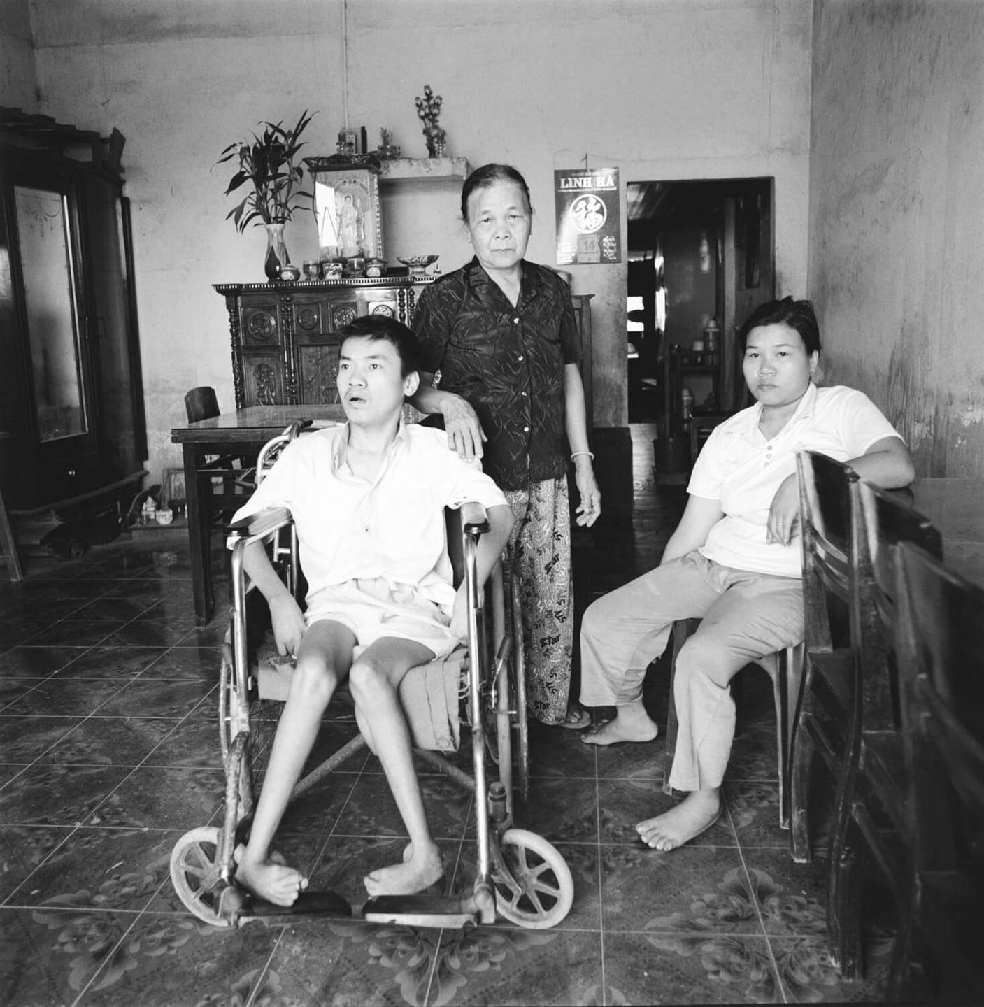 A deformed Asian man in a wheelchair with two Asian woman attending nearby.