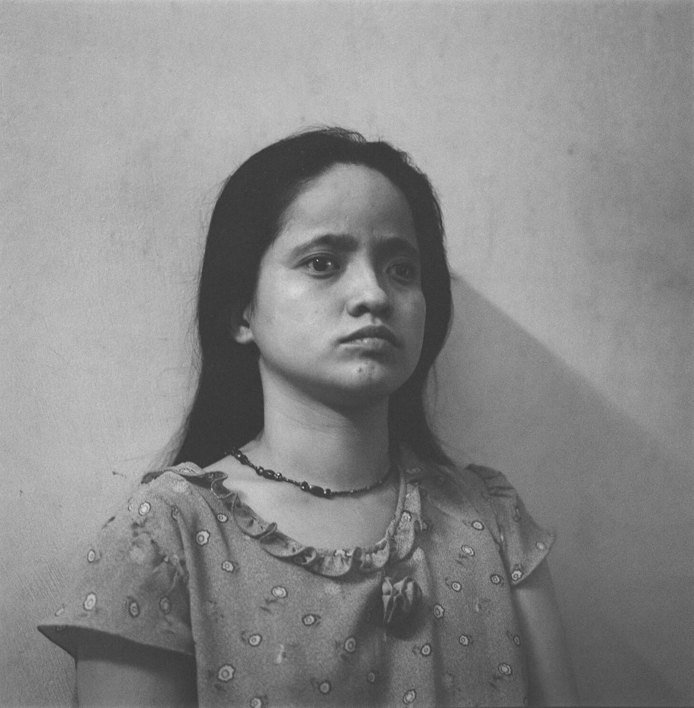 A young Asian girl looking dazed, against a wall.