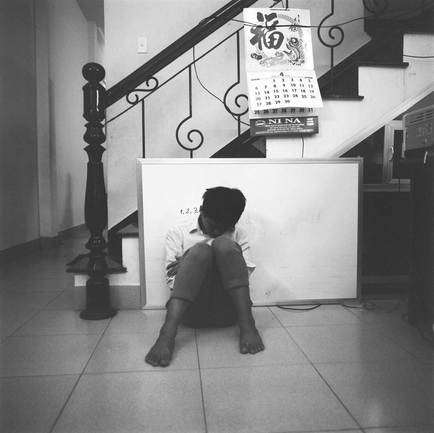 An Asian child slumped against a wall and seated on the floor.
