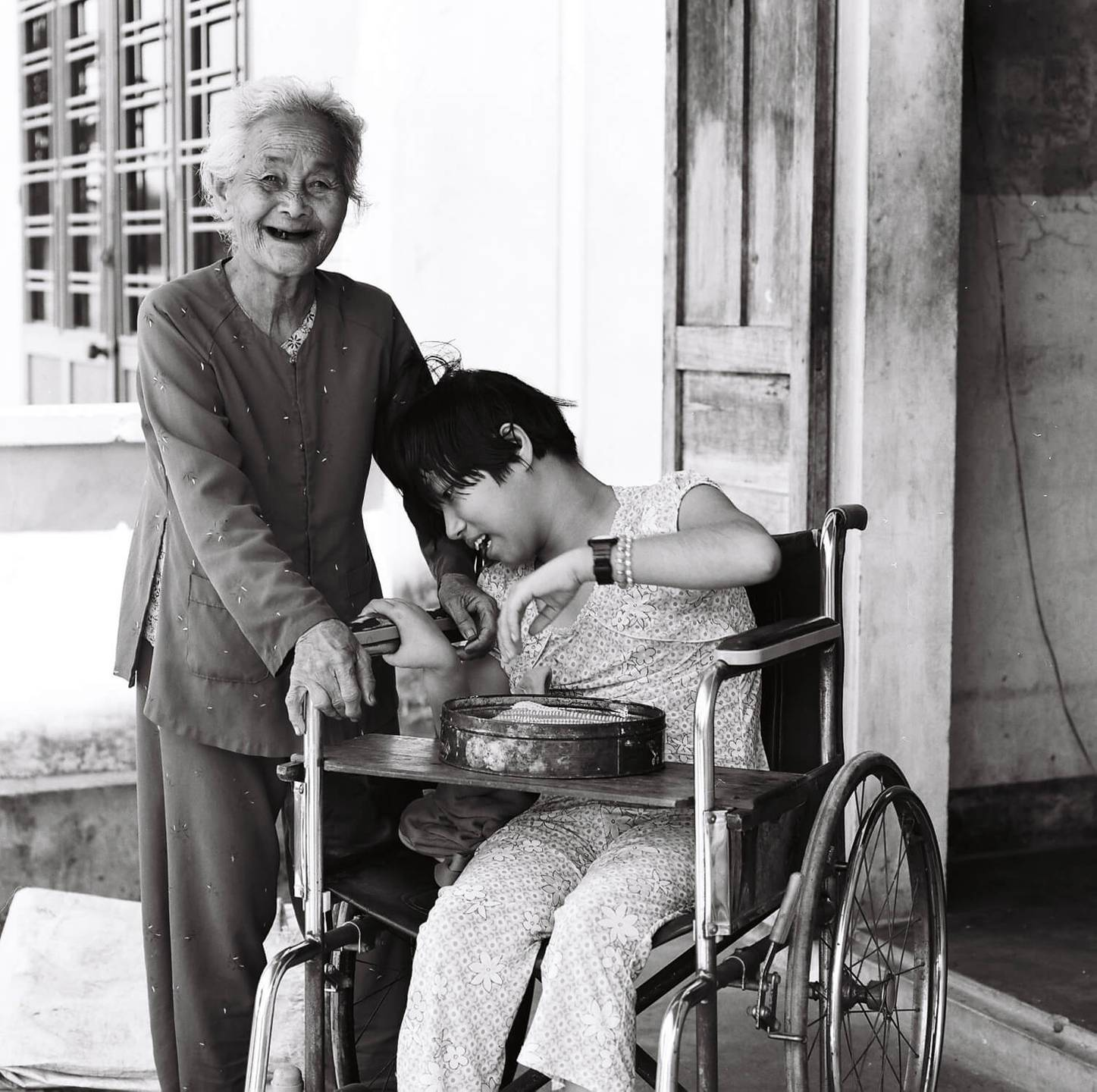 An old, smiling Asian woman standing at the side of a wheelchair-bound child.