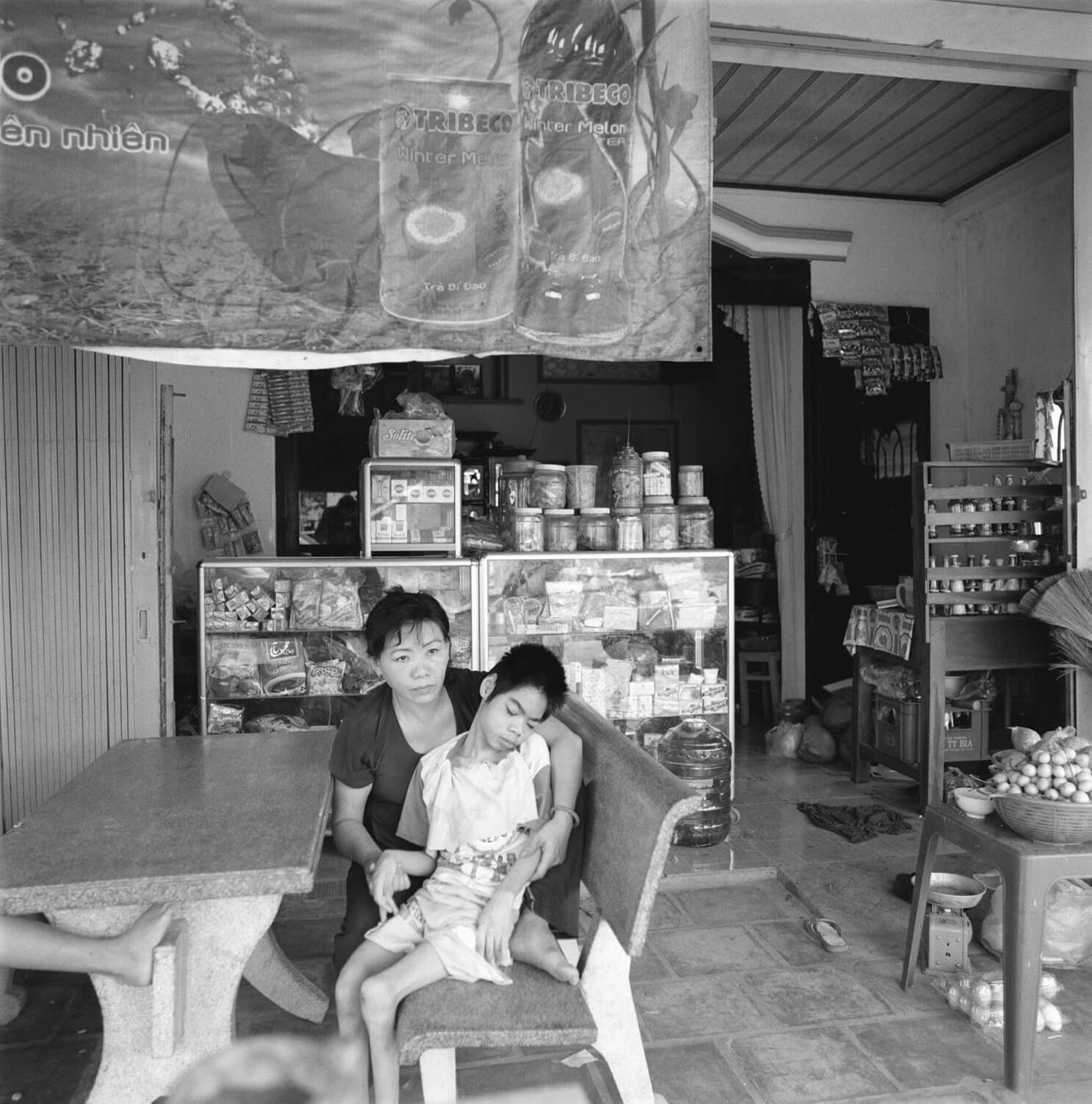 Asian mother and her deformed child, sitting in a booth at a shop or restaurant.