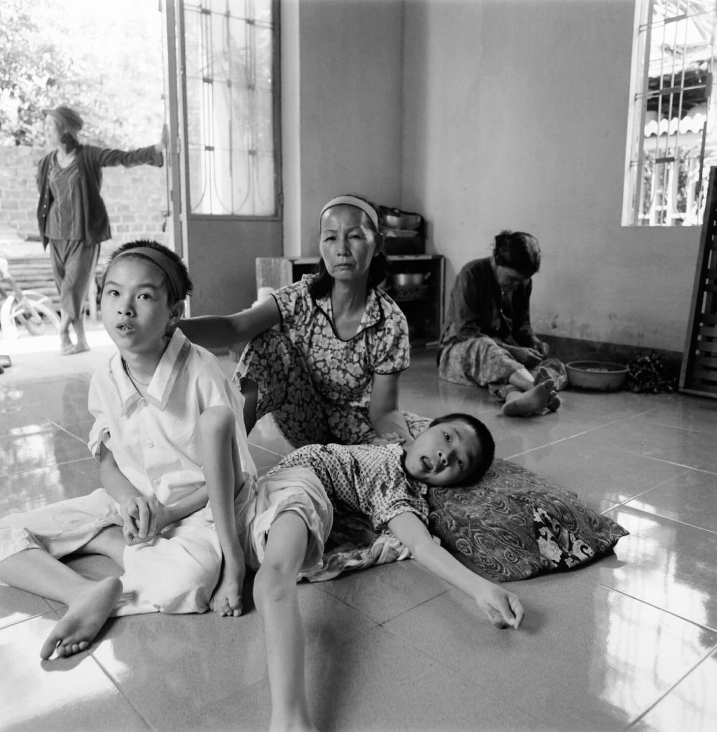 Asian family sitting on a tile floor. One child lays and his body is contorted.