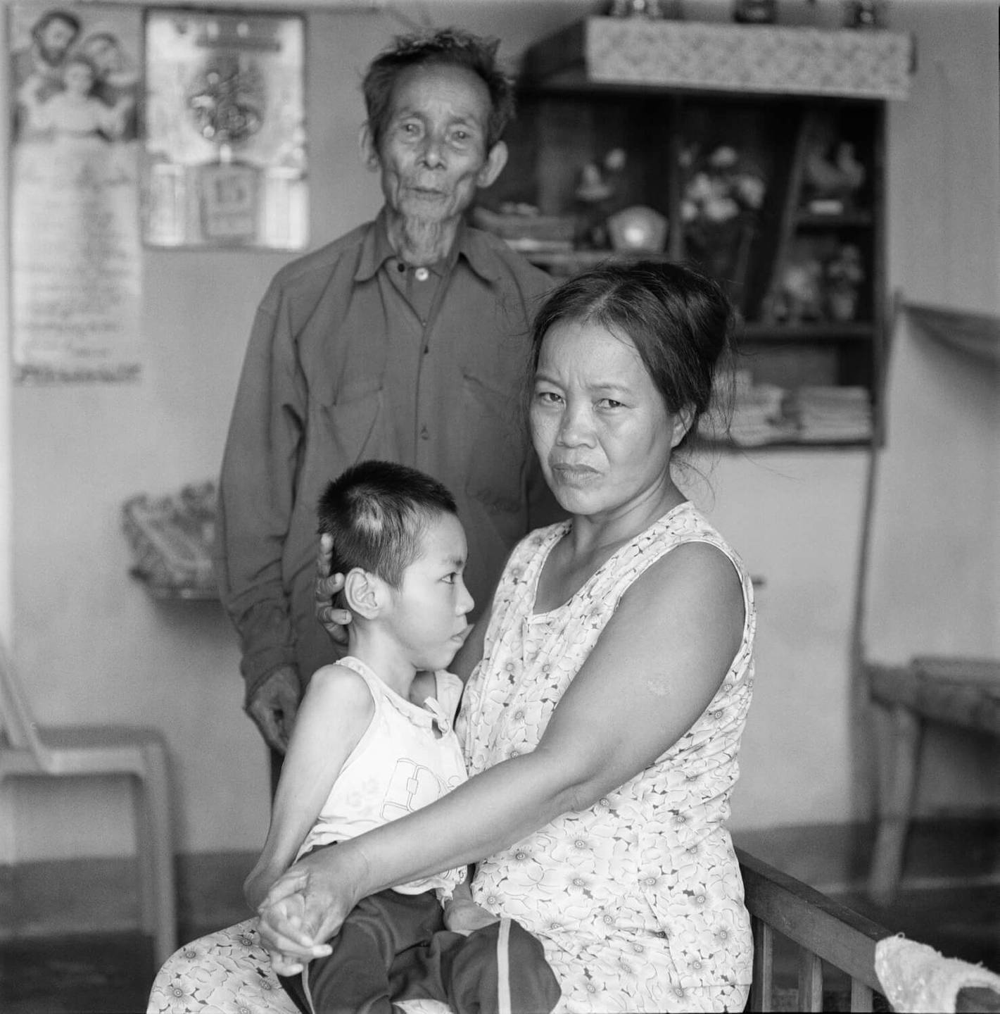 An older Asian man, a middle-aged woman, and presumably her son, deformed and sitting on her lap.