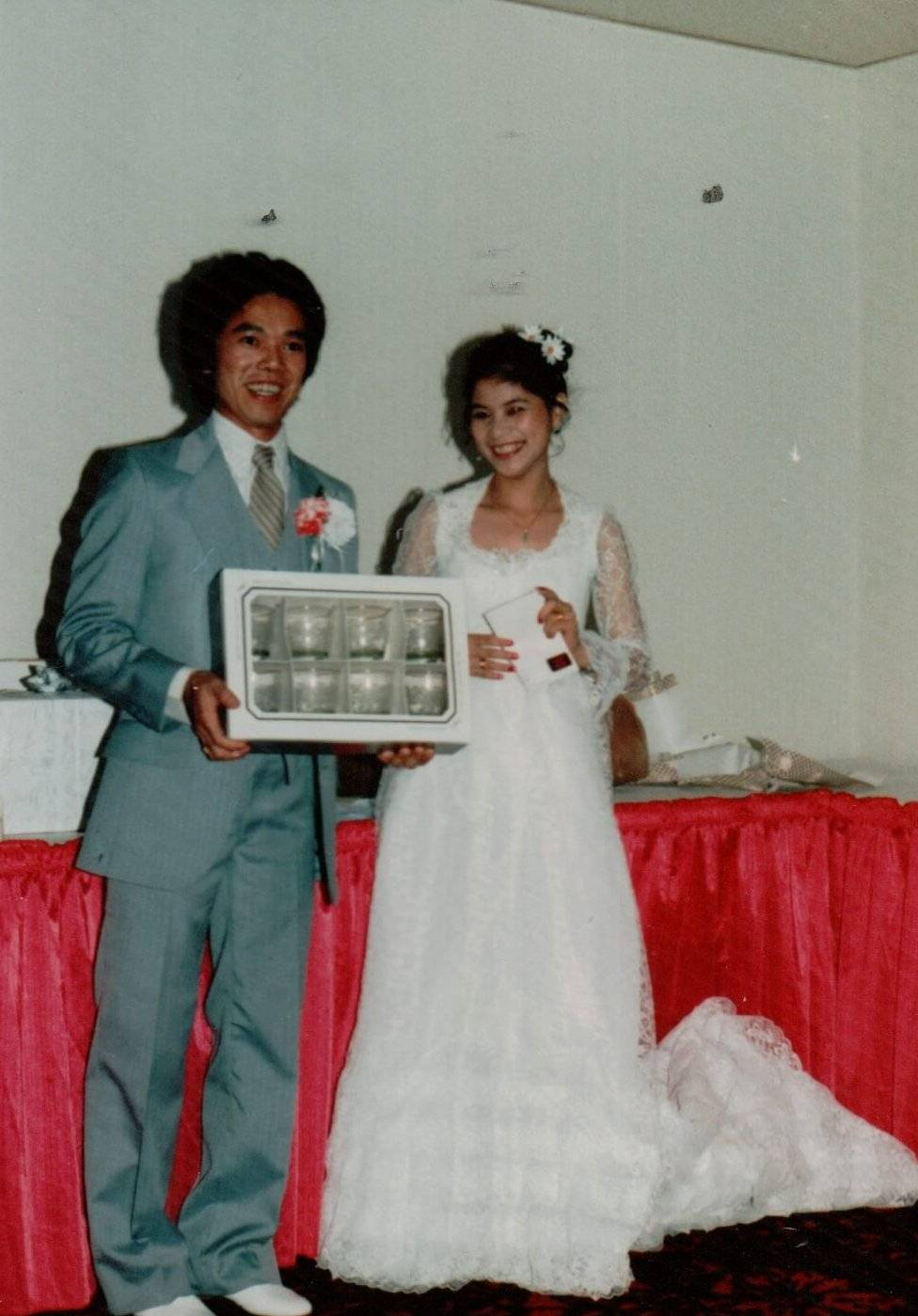 An Asian bride and groom holding up a gifted set of glasses.