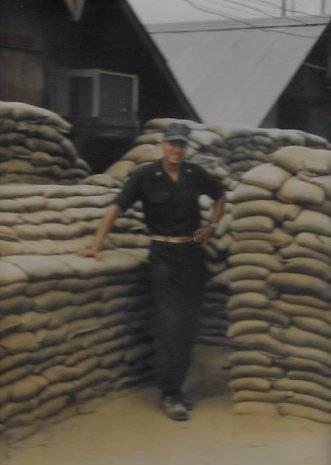 U.S. soldier standing among sandbags piled high.