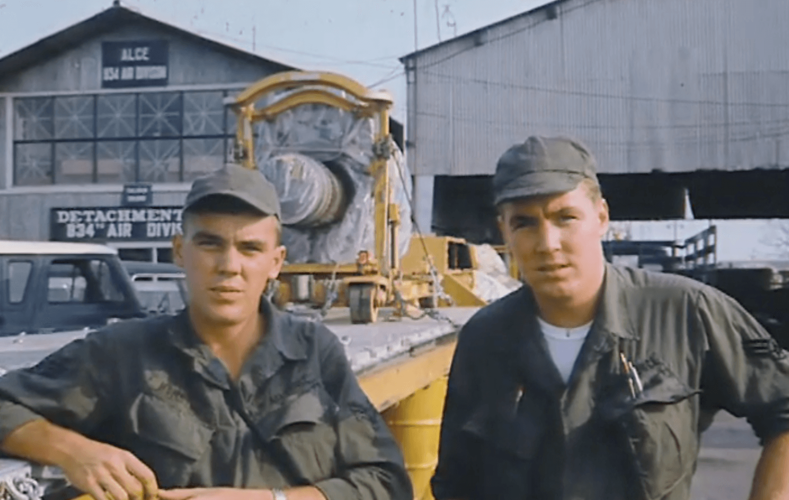 Two young US soldiers who look very similar, standing outside an Air Force base.