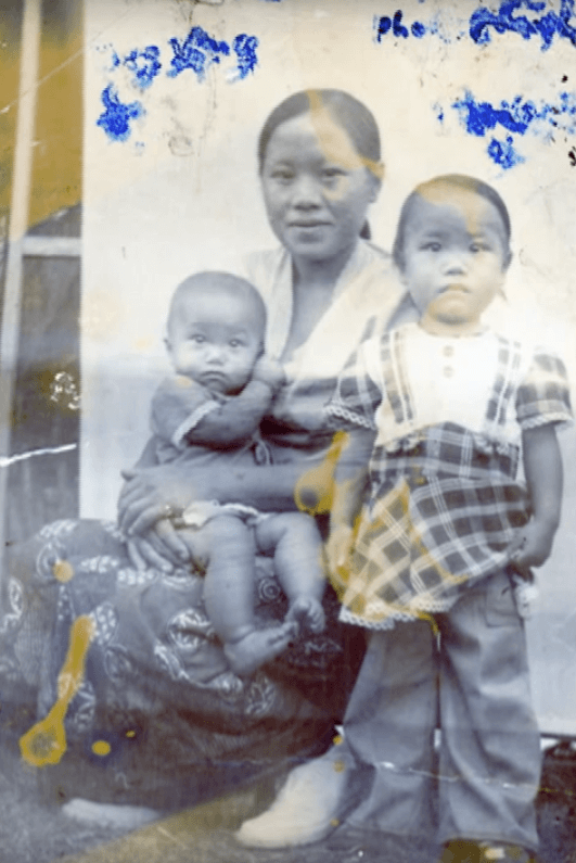 Portrait of a Hmong mother with two young children, image distorted by ink smudges.