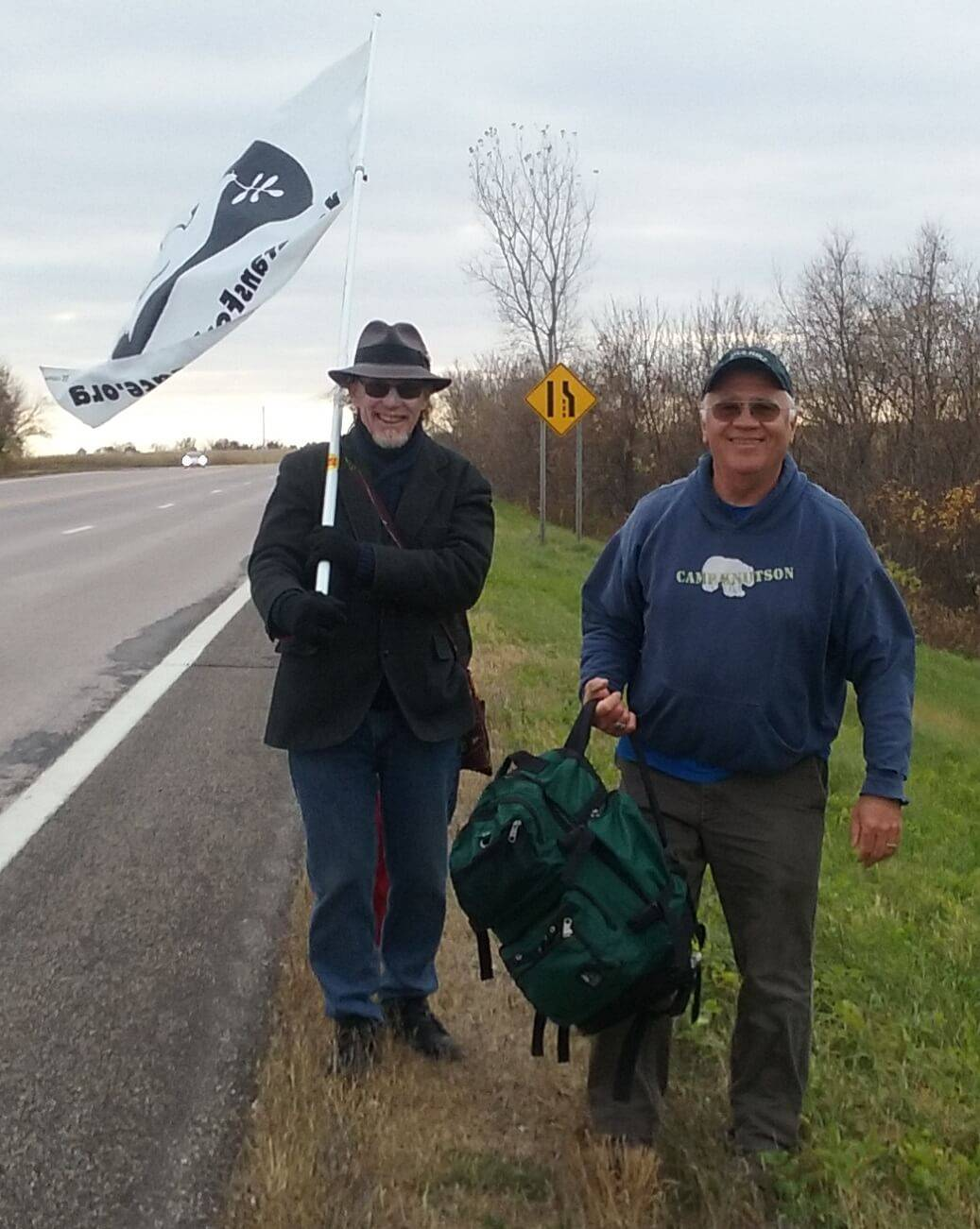 Two older gentleman, modern day, walking along the side of the road. One carries a Veterans for Peace flag.