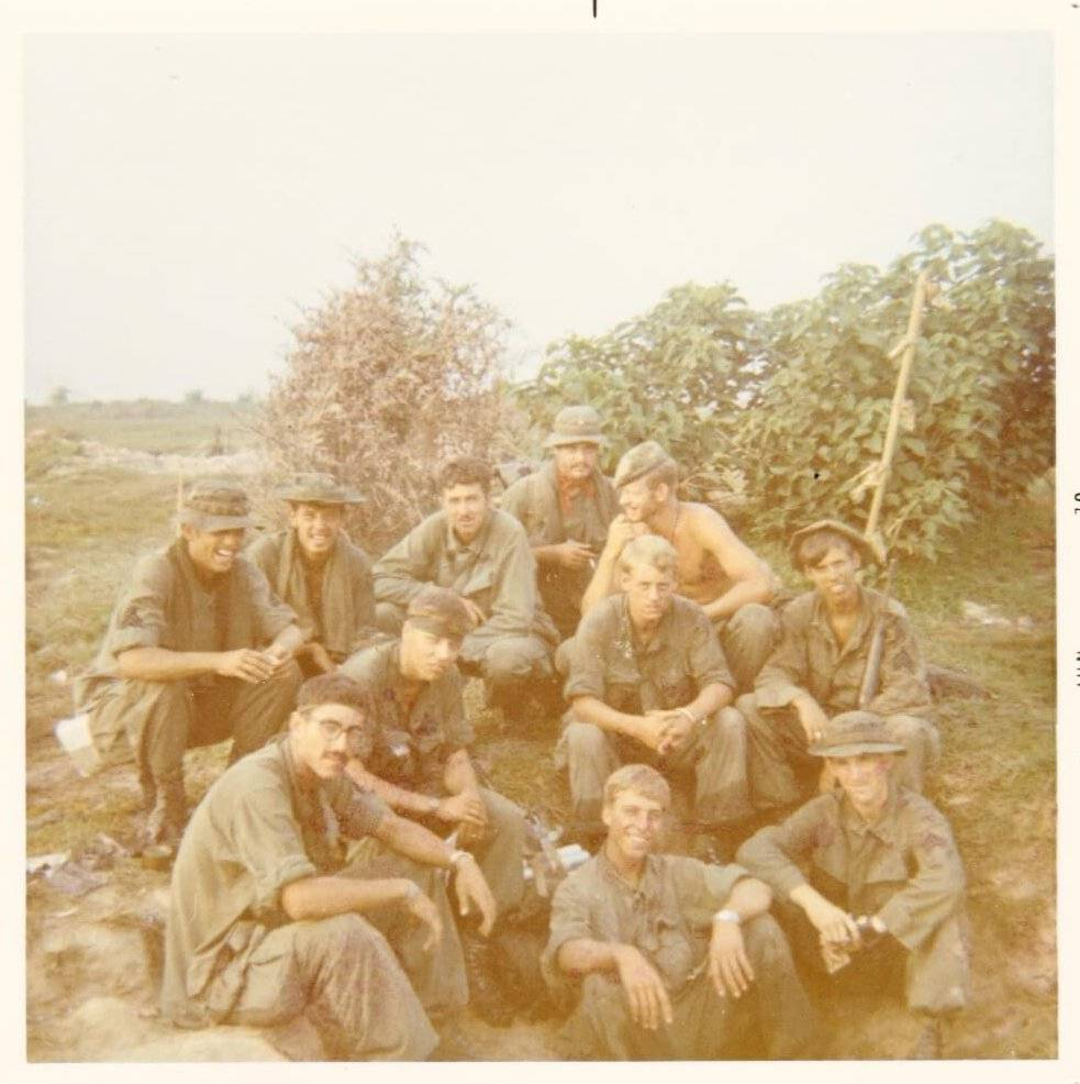 A group of U.S. soldiers hanging out in the wilderness.
