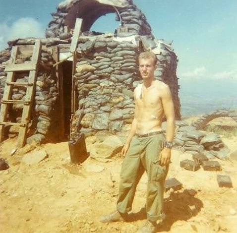 Young shirtless soldier standing outside a bunker.