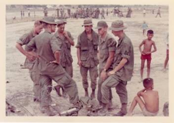 U.S. soldiers in fatigues, on a beach. Vietnamese children hang out nearby.