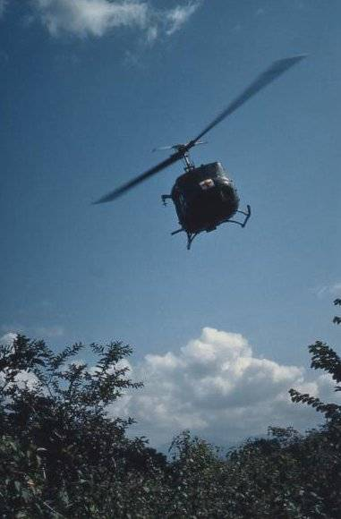 A helicopter with red cross on its nose, flying above some foliage.