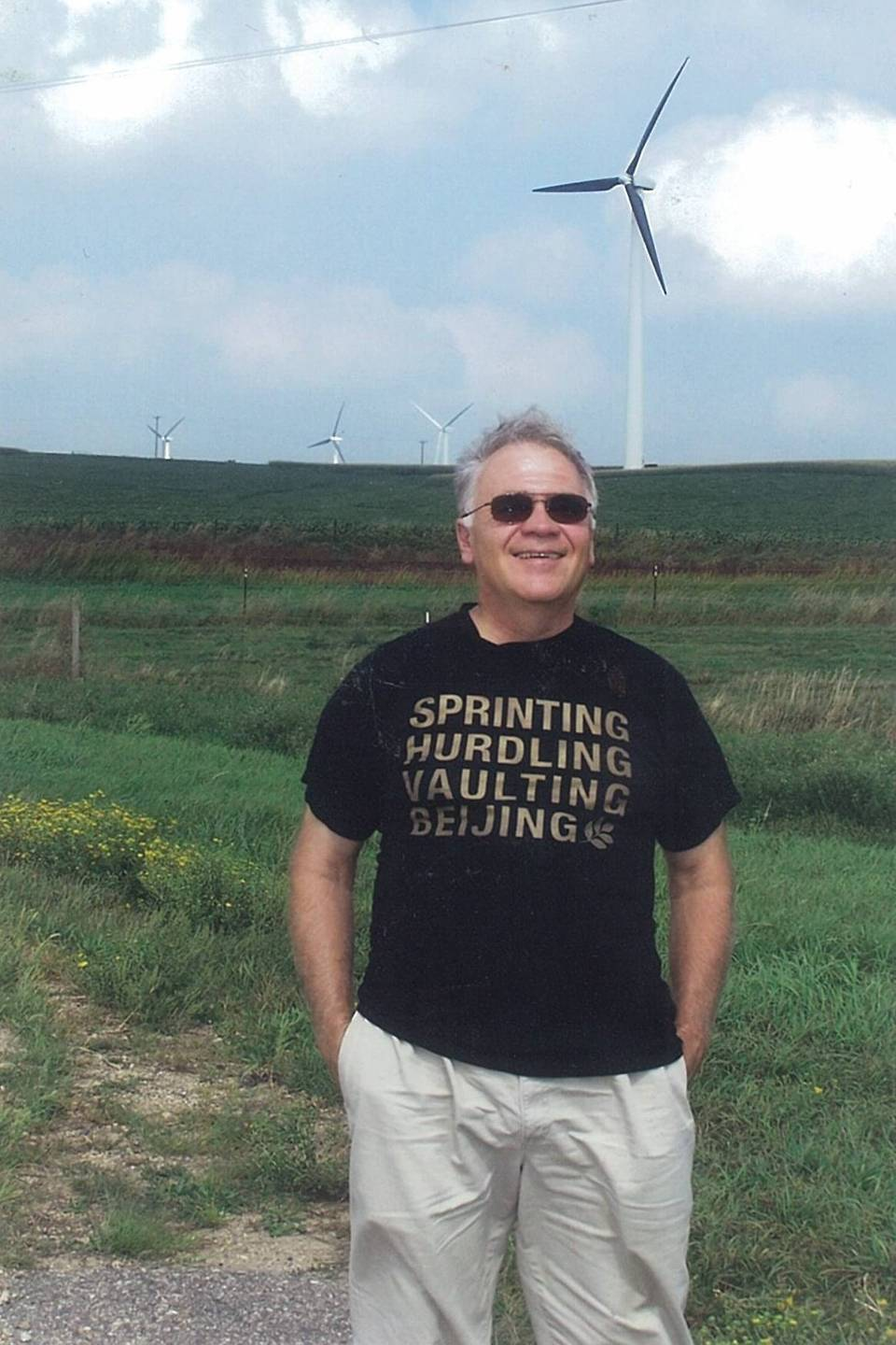 Older gentleman, modern day, standing in front of a field with a wind turbine.