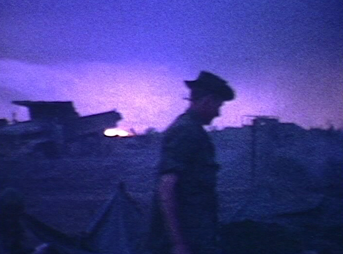 Silhouette of a soldier in a boonie hat against a blue, purple and pink sky.