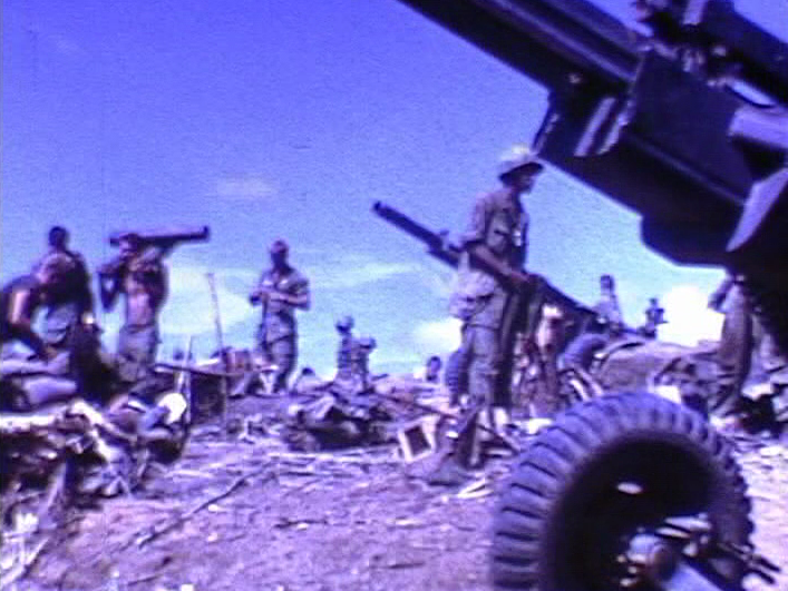 A cannon in the right foreground; several soldiers with various weaponry setting up in the background.