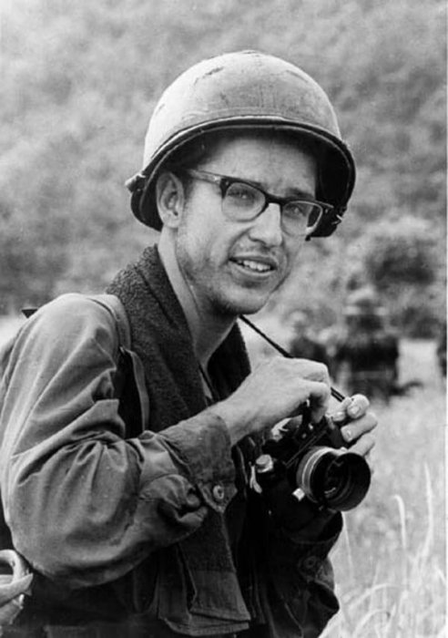 A young soldier with helmet on, camera around his neck.