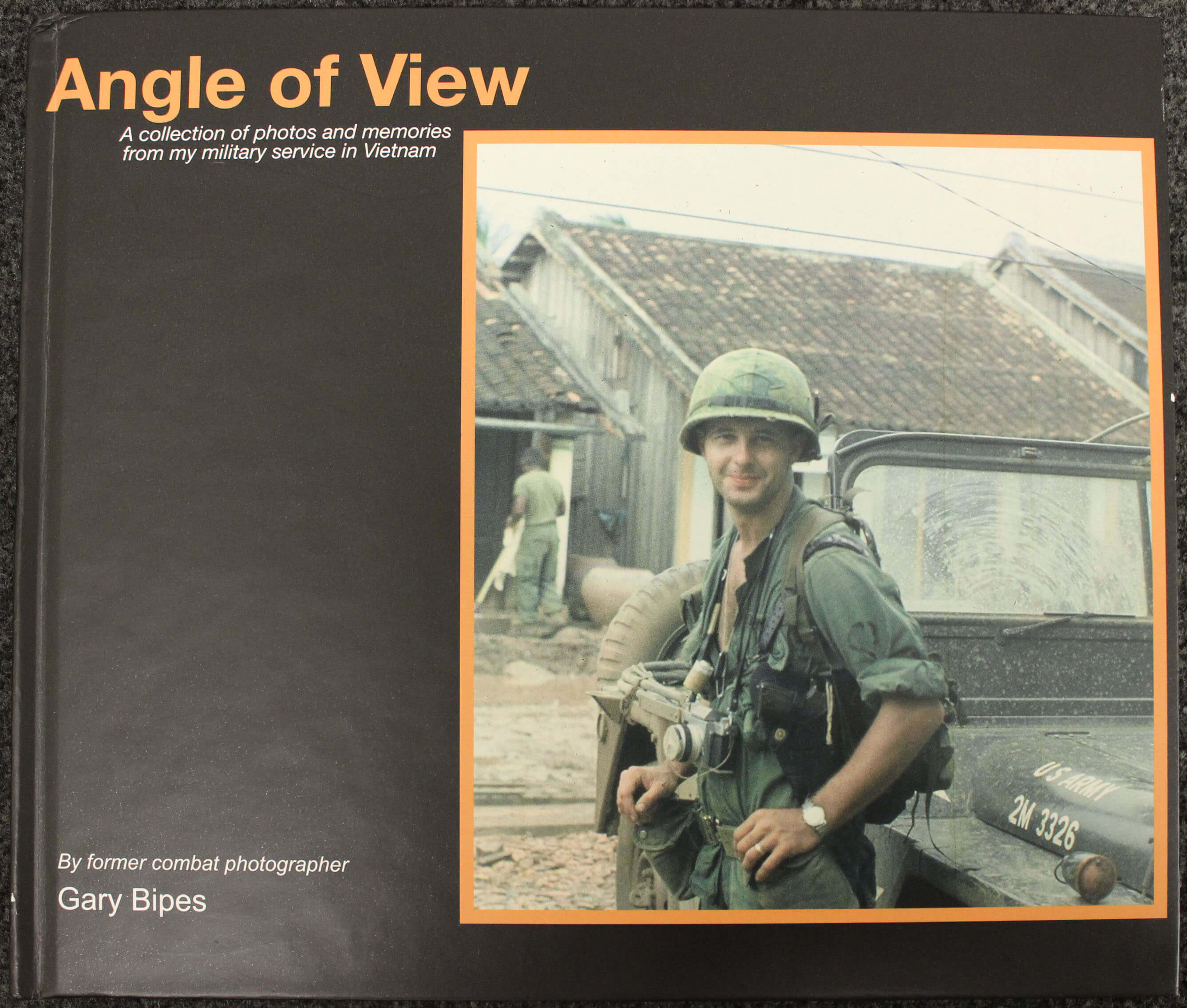 """Cover of a book: """"Angle of View: A Collection of Photos and Memories from my Military Service in Vietnam"""" - photo is of a young man in uniform and helmet with a camera around his neck."""