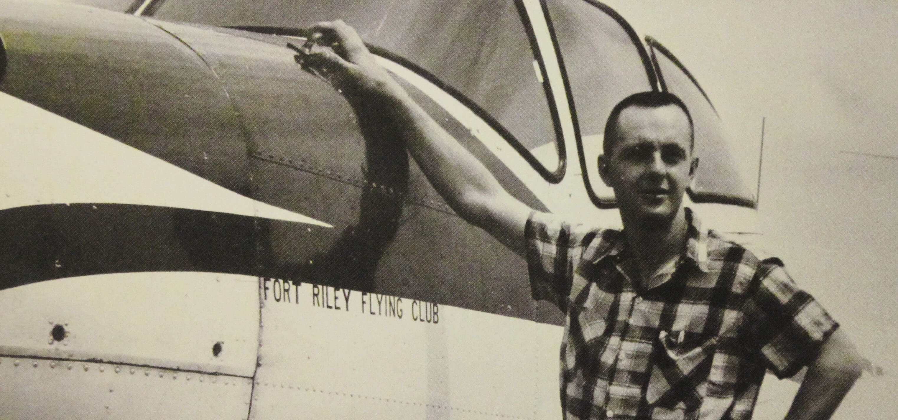 """A young man in civilian clothes leaning up against a plane with the text """"Fort Riley Flying Club"""" on its side."""