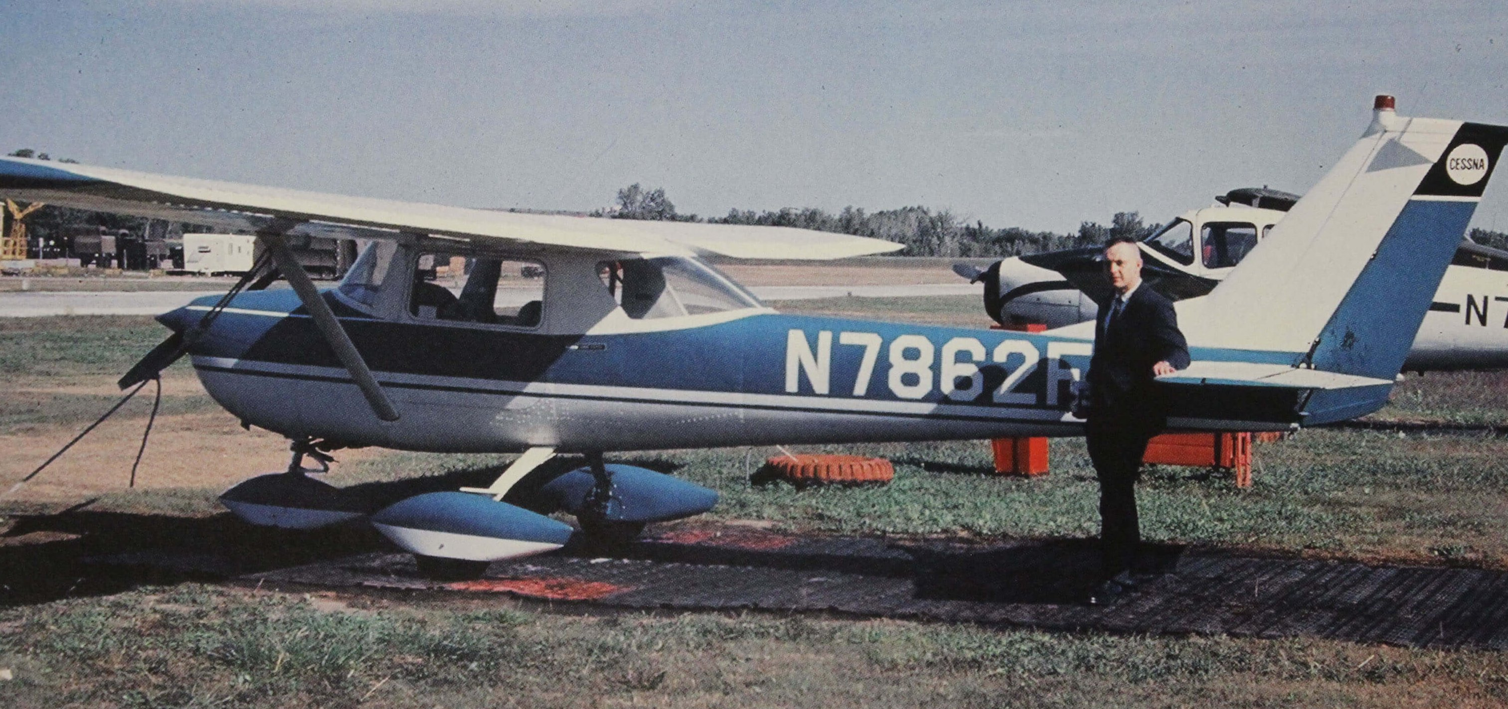 """A young man in a suit standing near the tail of a small plane with the text """"N7868F"""" on its side."""