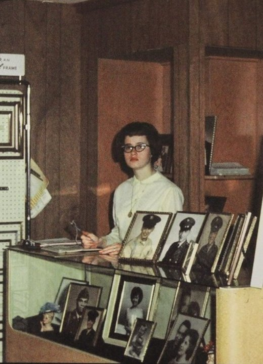 A young woman behind the desk of a photo shop, making notes on a clipboard.