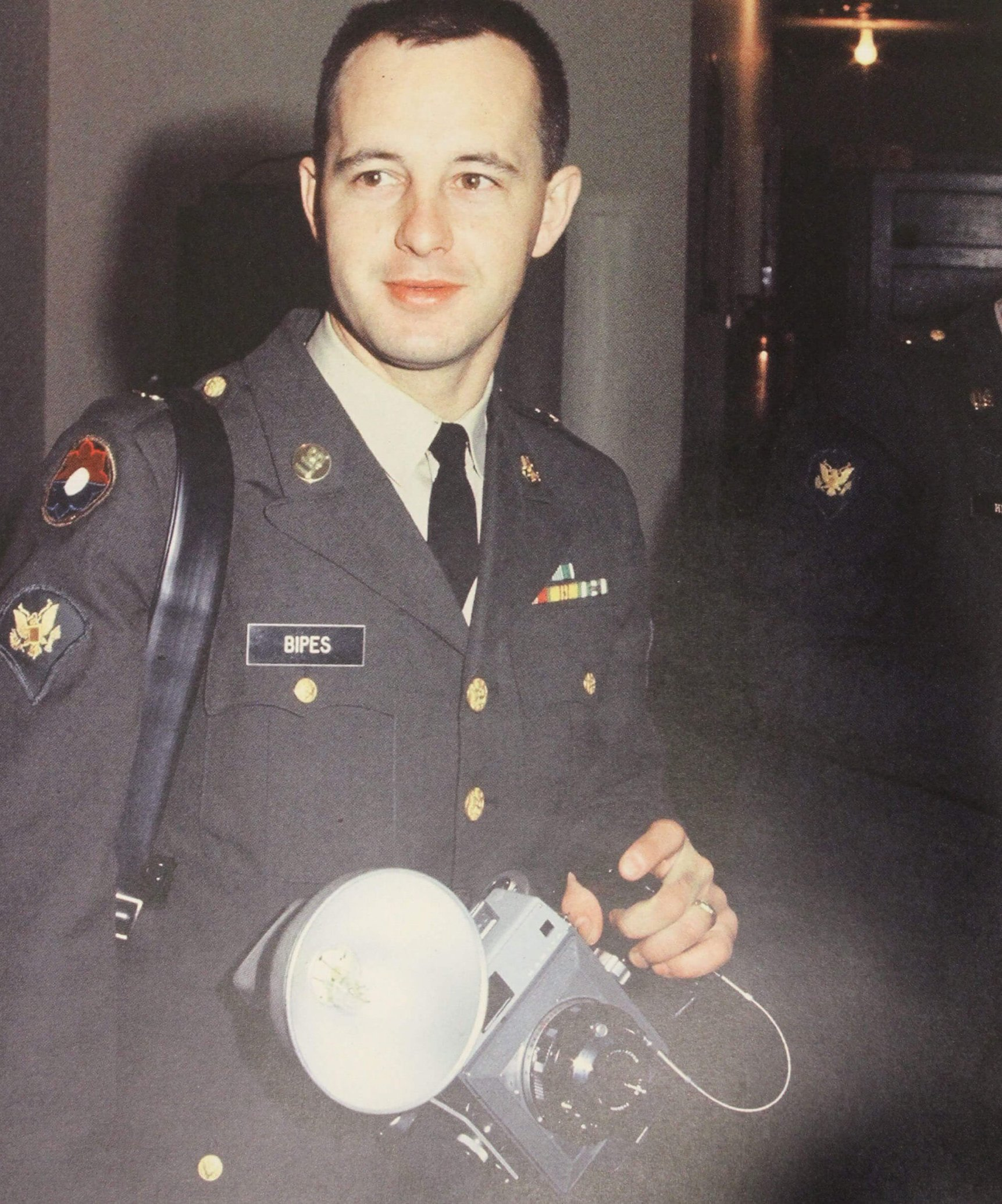 A young man in uniform with a camera in his hand.