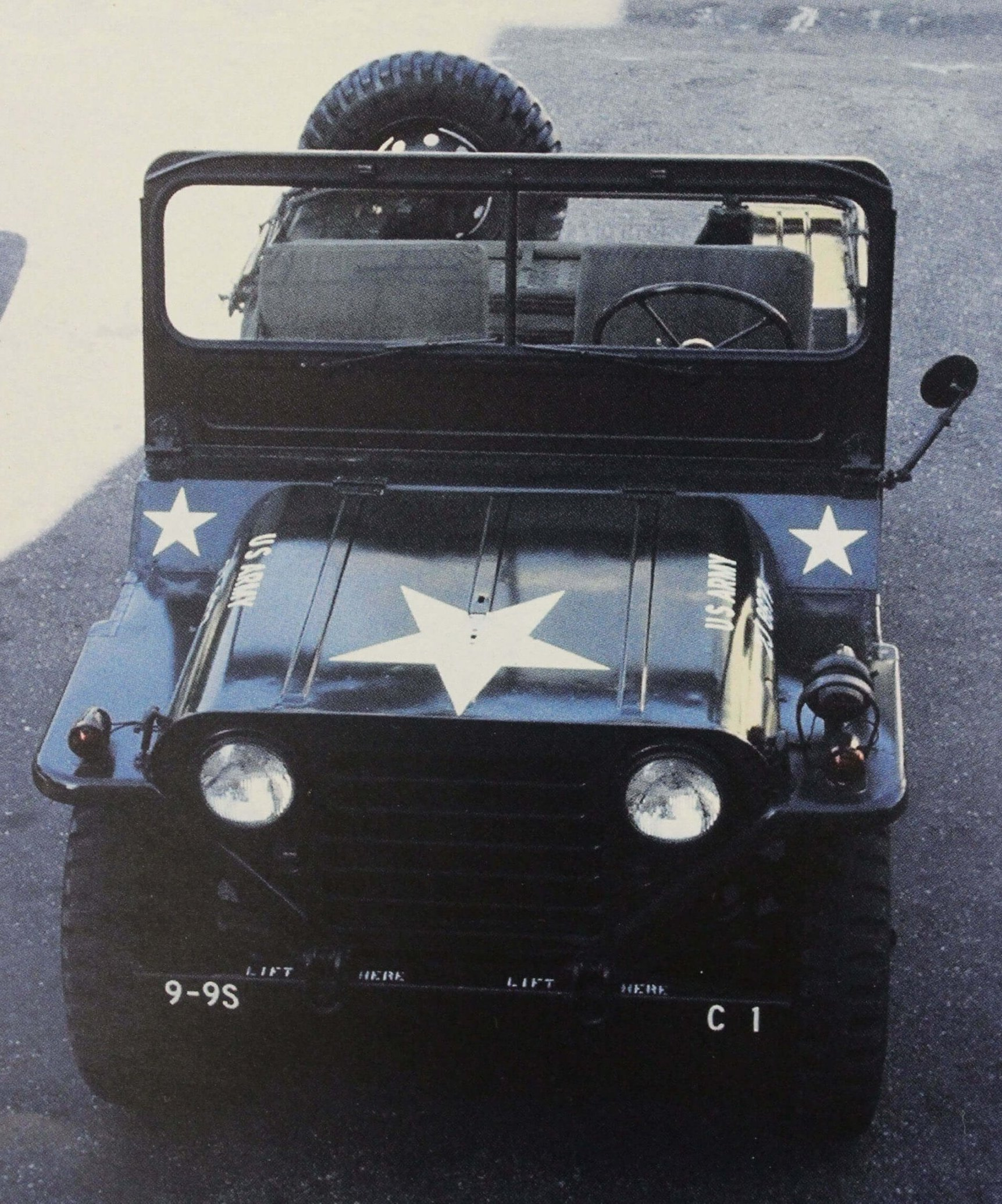 A black Army jeep with three white stars painted on it.