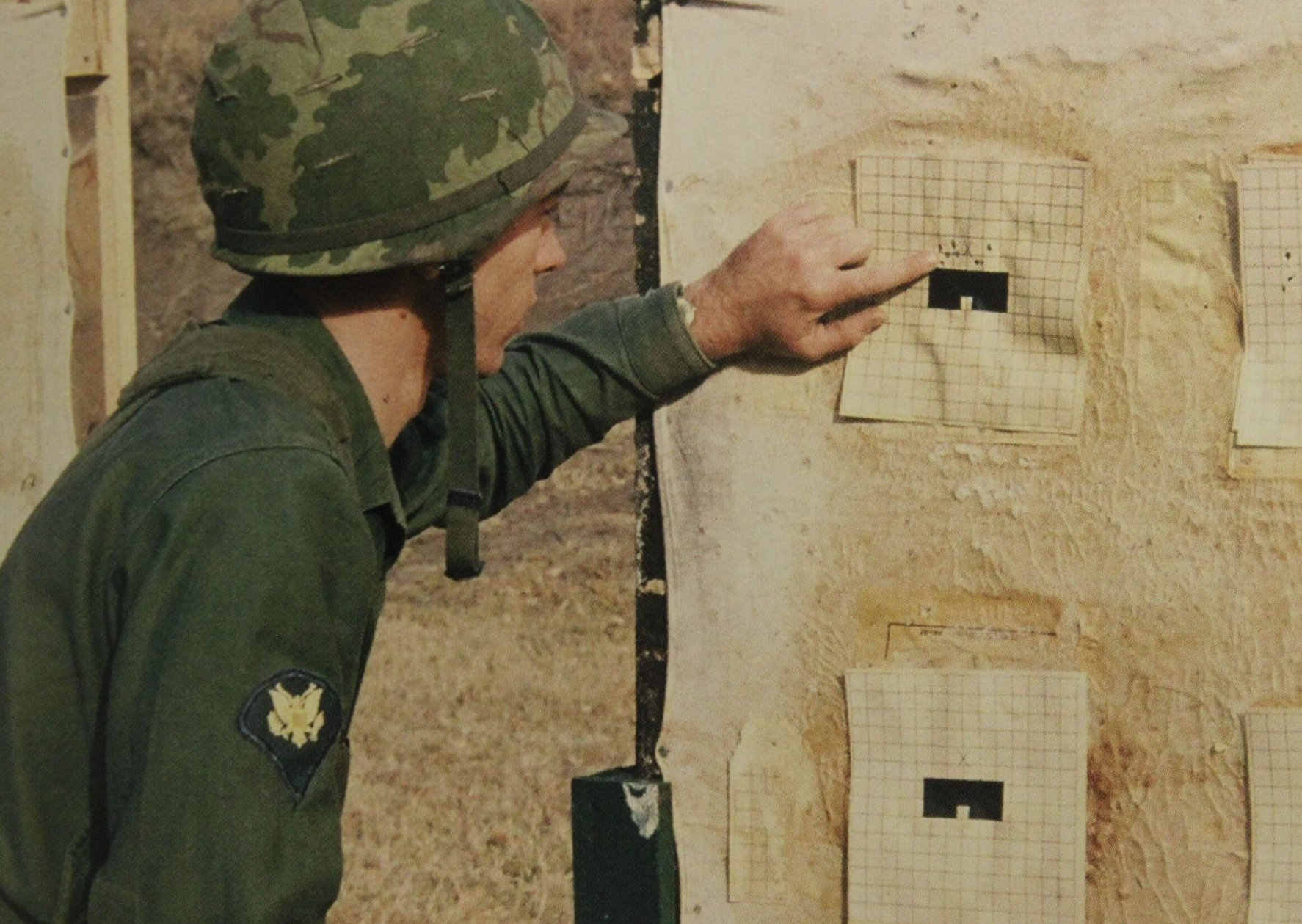 A young soldier looking up close at his target.