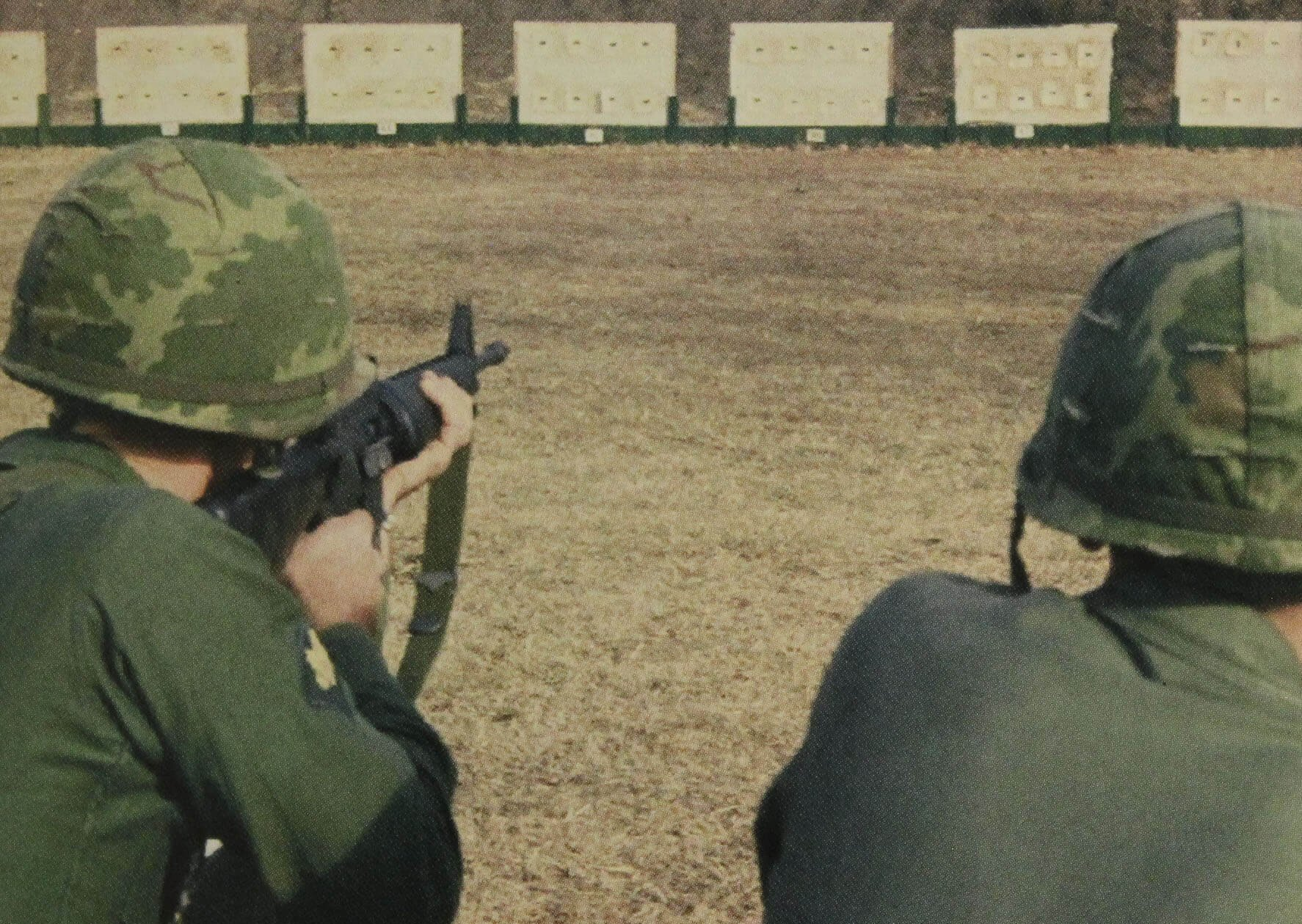 Two soldiers from behind, taking aim at far away targets.