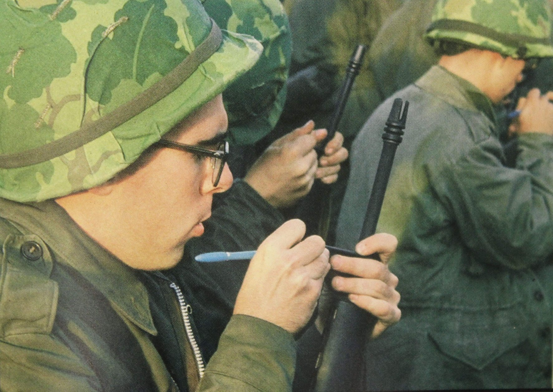 Young men inspecting their rifles, making marks on them.