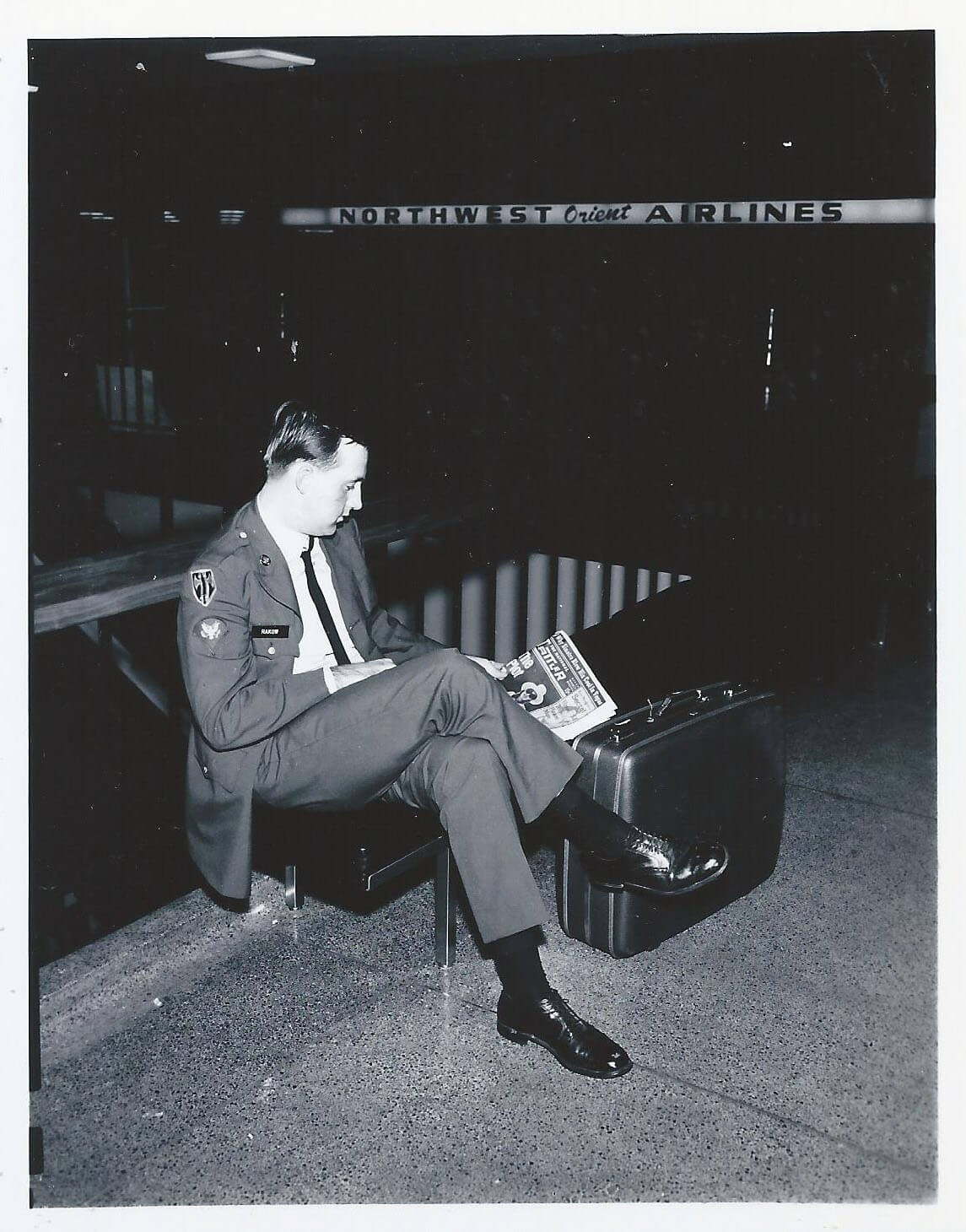 A soldier in his dress blues sits in an airport with his luggage, reading a newspaper.