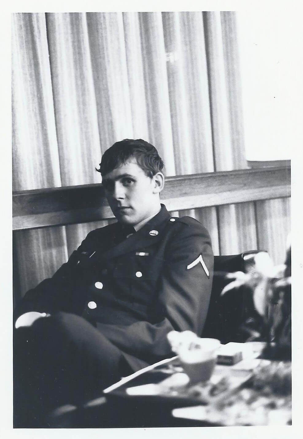 A young, sad-looking soldier looks into the camera.