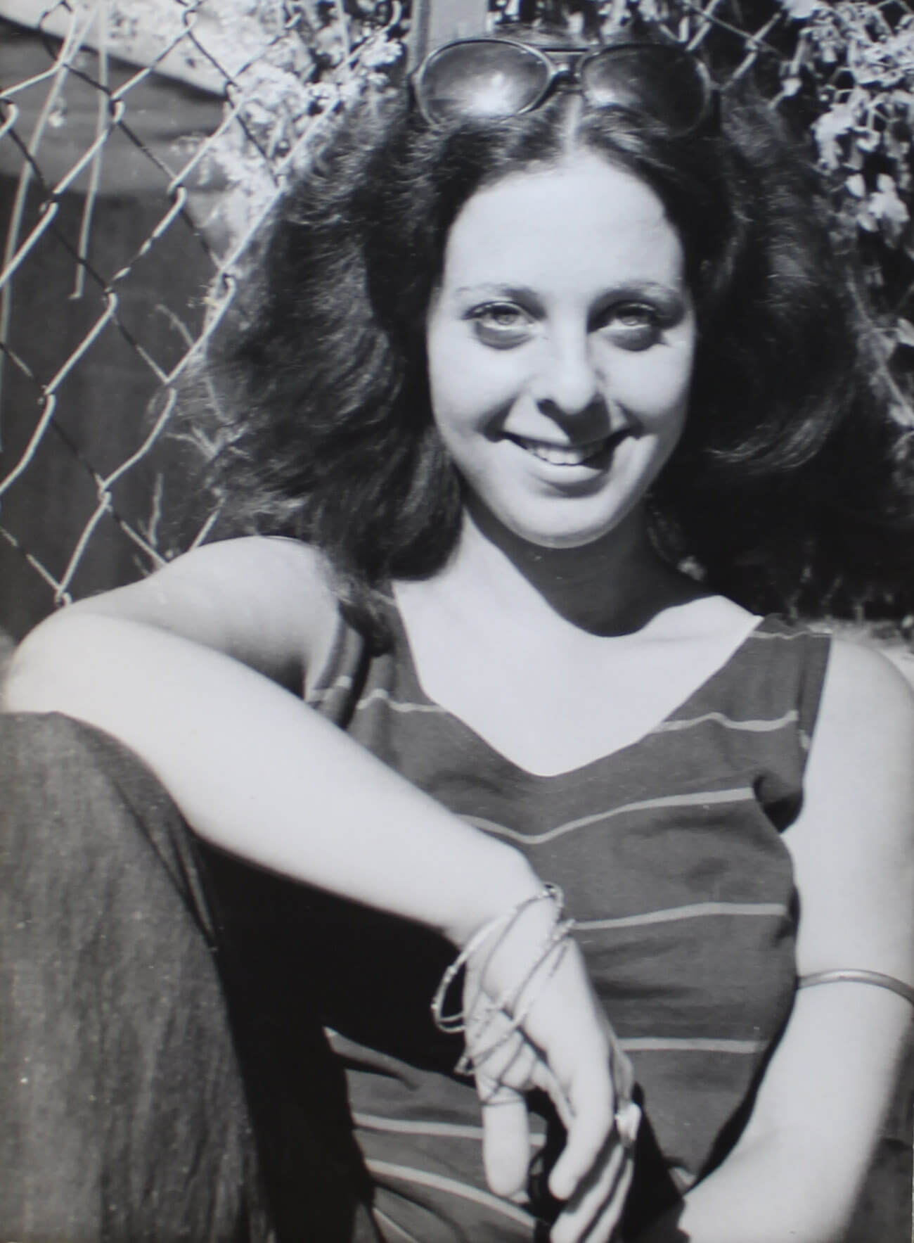 Photo of a young woman casually sitting against a chain-link fence in the summer.