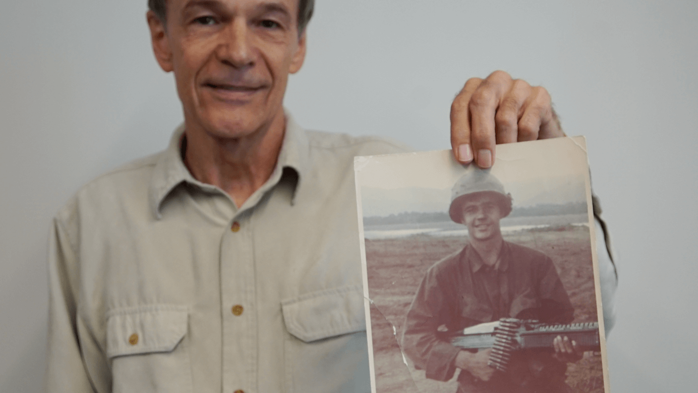 Man holding image of himself as a young soldier.