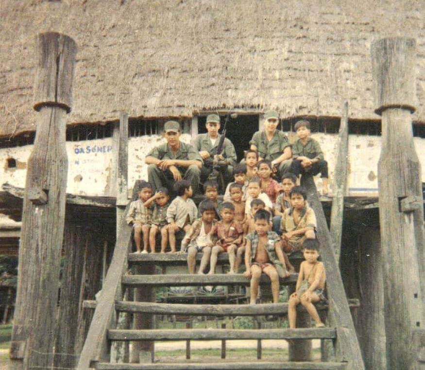 Young Vietnam soldier sitting on the steps of a thatched hut with a group of native children.