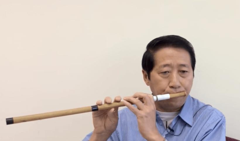 Hmong man playing a wooden flute.