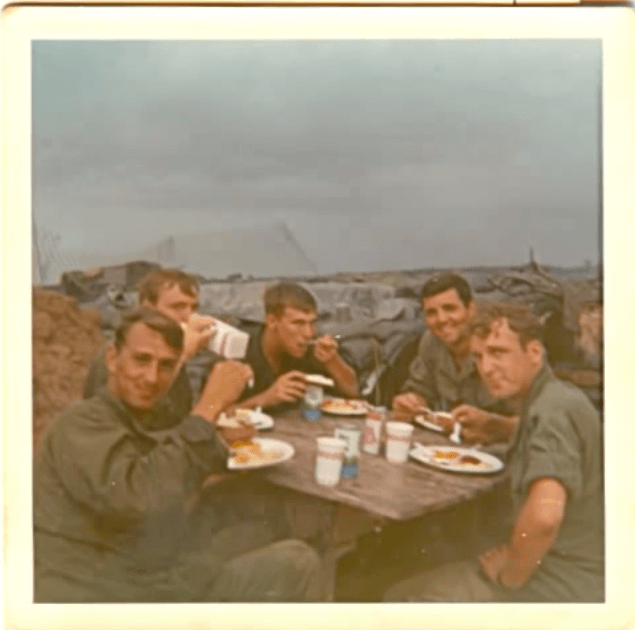 Young Vietnam soldiers sit at a table outside eating food.