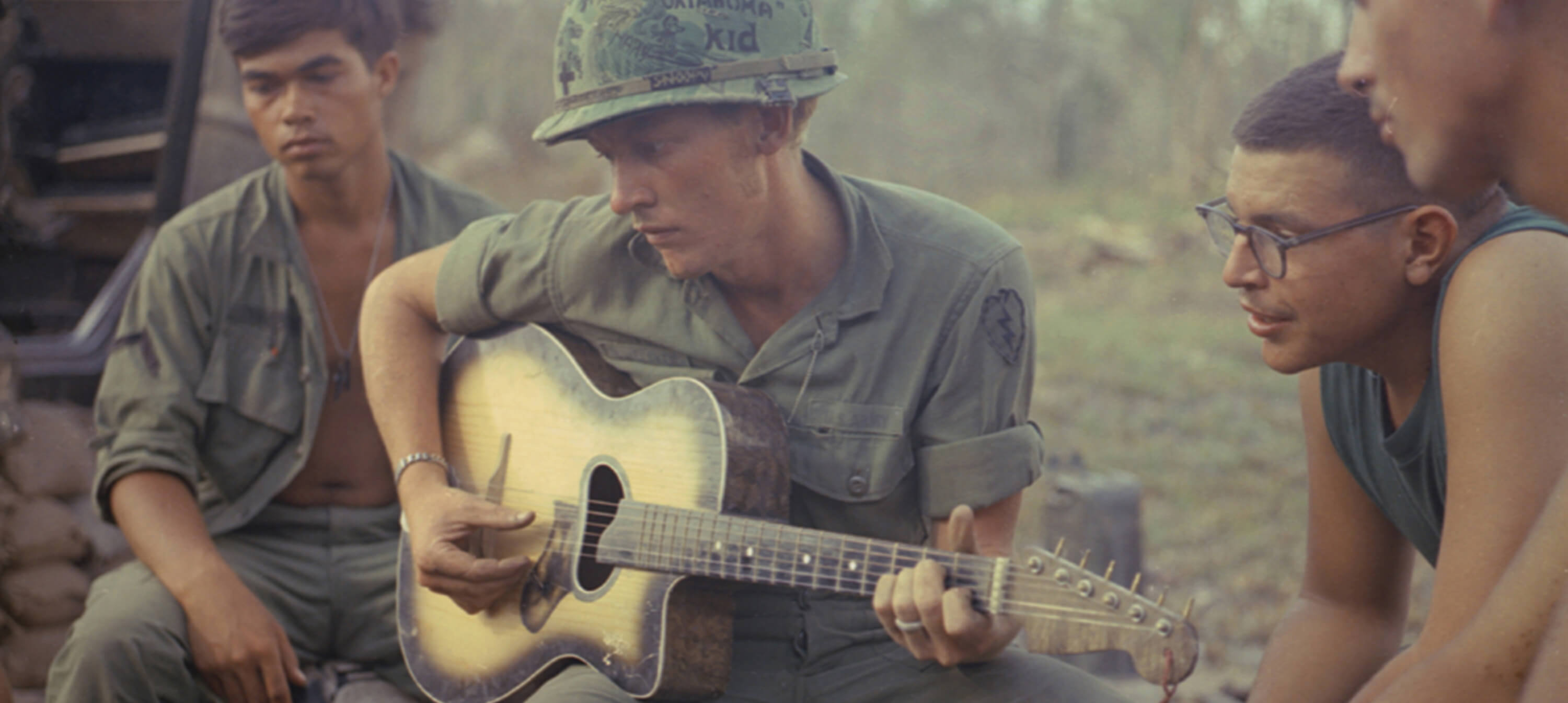 Vietnam soldiers listen to soldier playing guitar in camp.