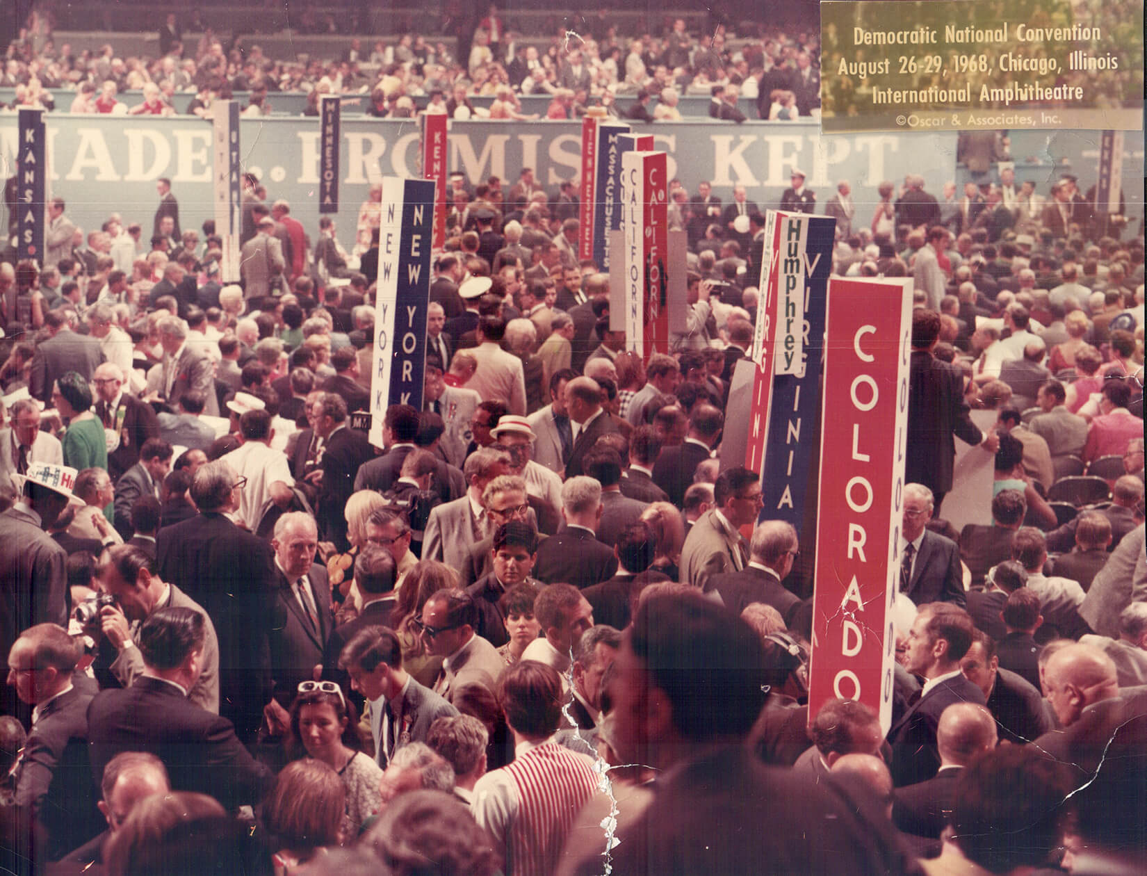 Color photo of a room of packed people, vertical red and blue state signs -- MN is blue -- and a credit in the upper right corner: Democratic National Convention, August 26-29 1968, Chicago, copyright Oscar and Associates, Inc.