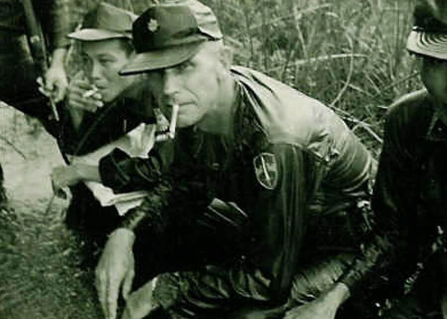 An older U.S. soldier crouched down with Asian soldiers, smoking a cigarette.